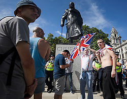 © Licensed to London News Pictures. 31/08/2019. London, UK. A group of Brexit supporters  form a counter demonstration underneath a statue of Former PM Winston Churchill, in Parliament Square as pro EU Protestors gather near 10 Downing Street in Westminster, London as part of a nationwide 'Stop The Coup' day of action against Boris Johnson's plans to suspend parliament. More than 80 demonstrations are planned across the UK in response to government plans to prorogue parliament. Photo credit: Ben Cawthra/LNP