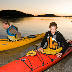 Two kayakers put on their spray skirts at dawn in Bar Harbor, Maine.