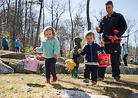 Lexi leads the way into a patch of Easter Eggs during the Weirs Beach Community Center's Easter egg hunt on Saturday morning.  (Karen Bobotas/for the Laconia Daily Sun)