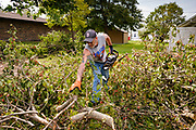 """12 AUGUST 2020 - SLATER, IOWA: DENNIS KOMMES uses a chain saw to clear debris in a residential neighborhood in Slater Wednesday, more than 48 hours after a windstorm ripped through the community. According to Iowa Governor Kim Reynolds, the storm damaged 10 million acres of corn and soybeans in Iowa, about 1 one-third of Iowa's 32 million acres of agricultural land. Justin Glisan, Iowa's state meteorologist, said the storm Monday, Aug. 10, lasted 14 hours and traveled 770 miles through the Midwest before losing strength in Ohio. The storm was a seldom seen """"derecho"""" that packed straight line winds of nearly 100MPH. The storm pummelled Midwestern states from Nebraska to Ohio.     PHOTO BY JACK KURTZ"""