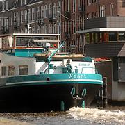 NLD/Amsterdam/20070515 - Grote boot vaart door de grachten en passert een brug midden in Amsterdam, terwijl de tram staat te wachten