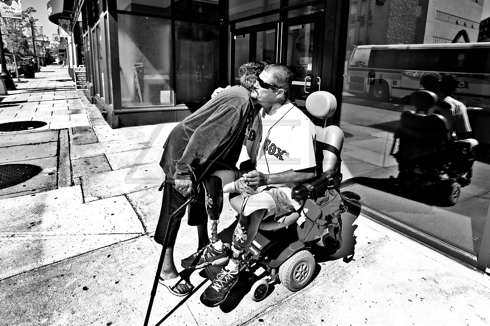 An aquaintance gives Carlos a hug as he waits at the bus stop for a ride to the dialysis clinic.  Carlos Raposa, 47, has had both of his legs amputated from the knees down after complications from diabetes.  He is also currently undergoing dialisys treatment 3 times/week for 3 hours sessions.  508-567-7793  As his condition has worstened over the years Carlos has had greater difficulty dealing with his condition.  Increasingly, Carlos has fallen greater into depression and has turned to smoking and drinking to deal with it.  What used to be monthly visits to the hospital has turned into weekly excursions with ever longer stays in hospital.  Family members have become ever more worried about Carlos' drop in weight and his inability to move on his own any longer.  For someone who was an athletic figure, Carlos has become a shadow of his former self.