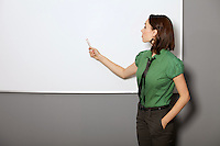 Businesswoman with hands in pockets pointing at whiteboard in office