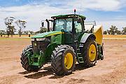 John Deere 7280R tractor with Krone hay baler in a field near Nurrabiel, Victoria, Australia.