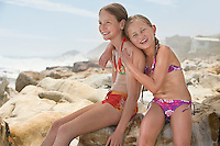 Two girls (7-9 10-12) sitting on rock on beach