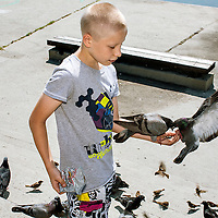 On a hot summer day, a boy is feeding doves at the bank of Angara river. - To purchase a limited-edition print, please contact us at martin@martinvondendriesch.com