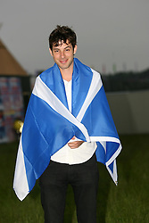 Mark Ronson, the British DJ, guitarist, and music producer, wears a Scottish flag backstage at Rockness 2007.