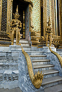 Yaks (fearsome giants) and five-headed naga serpents protect the Phra Mondop building, part of Wat Phra Kaew/Temple of the Emerald Buddha, at the Grand Palace, Bangkok, Thailand. King Rama I built Phra Mondop to house the revised edition of the Buddhist Canon. The walls of the Phra Mondop are covered in green mirrored tiles inlaid with gold medallions depicting Buddha. The base of the walls are lined with two rows of small gilded guardian angels, each one slightly different. Four corners of Phra Mondop hold stone Buddhas carved in the ninth century Javanese style. Sixteen twelve-cornered columns support the intricate multi-tier roof.