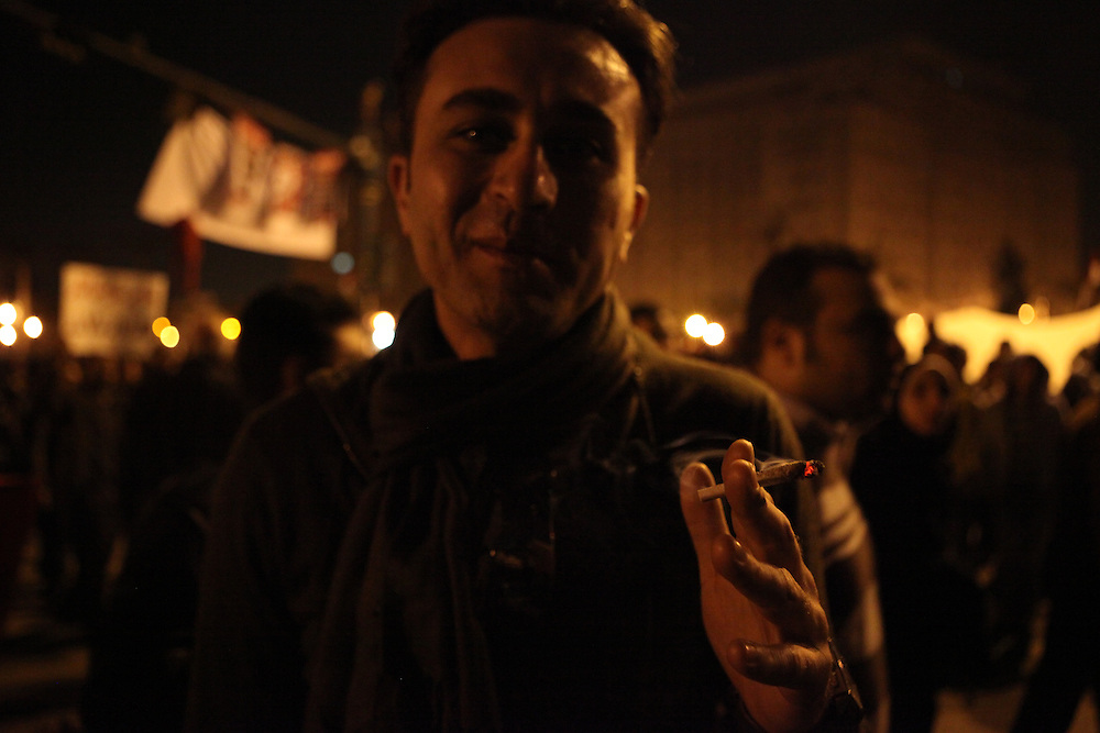 A man shows off that for the first time he's able to smoke hashish in the public at Tahrir Square, 9 February.