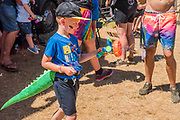 A boy with a dinosaur tail is entertained by the bubble gun from Bubble inc -The 2018 Latitude Festival, Henham Park. Suffolk 14 July 2018