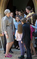 © Licensed to London News Pictures.16/04/2017.Reading, UK. Prime Minister Theresa May is surround by members of the congregation as leaves church with her husband Philip (L) after attending an Easter Sunday service in her constituency.Photo credit: Peter Macdiarmid/LNP