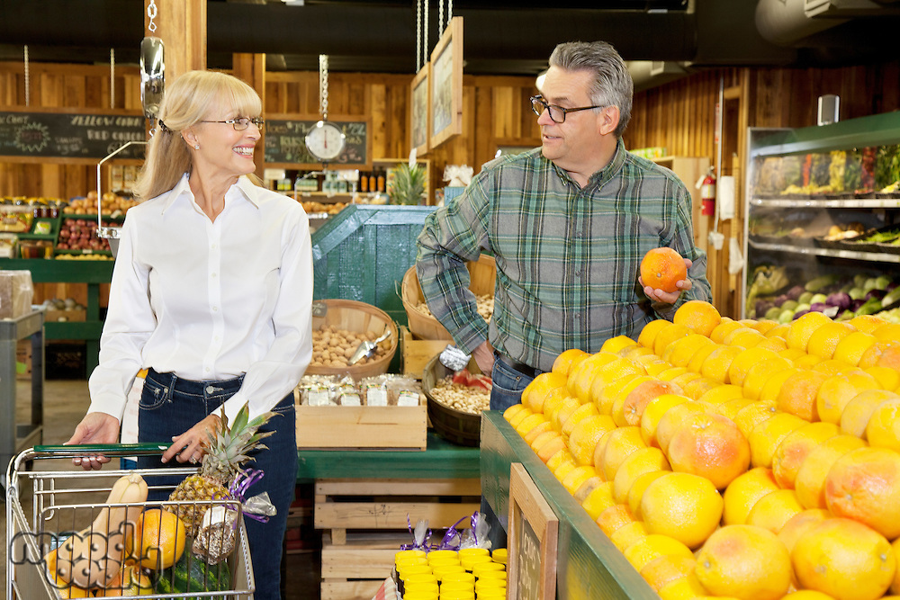 Couple looking at each other while selecting fruit in farmer's market