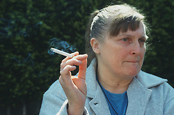 Woman standing outside smoking cigarette,