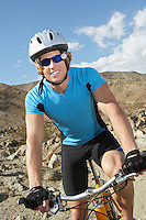 Young man on bicycle in mountains, portrait