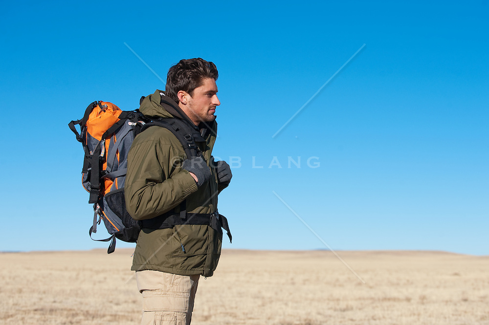 Profile of a man wearing a jacket and backpack standing in an open field