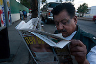 29 April 2009, Mexico City, Mexico--- A man reads a newspaper proclaiming that 159 people have so far died from the disease outside the Gustaro Baz Prada Hospital in Neza in Mexico State --- Image by © Trevor Snapp