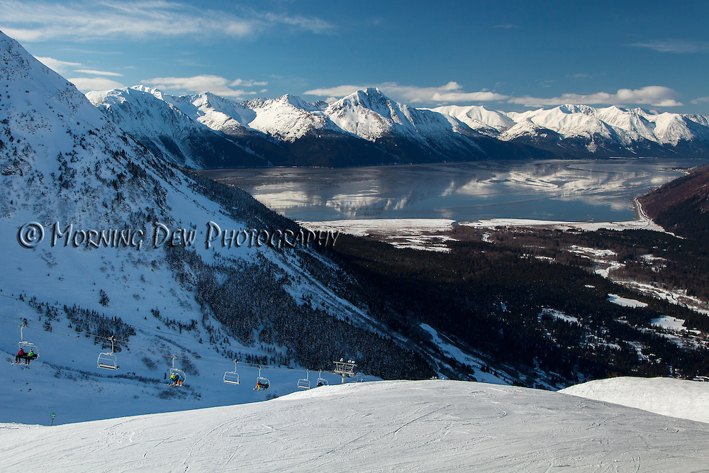 The mountains of the Kenai Peninsula reflect in the unusually calm waters of Turnagain Arm as skiers ride the lift to the top of the run at Alyeska Ski Resort in Girdwood, Alaska.