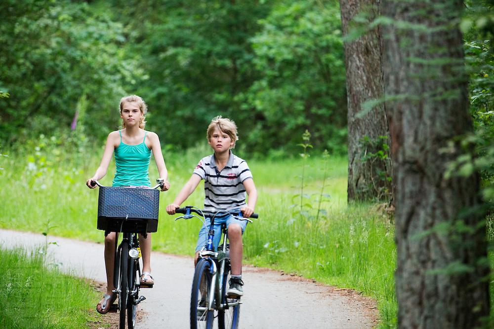 In Soest fietsen een jongen en een meisje door de bossen van natuurgebied Soesterduinen.<br /> <br /> In Soest a young boy and girl cycle in the woods.
