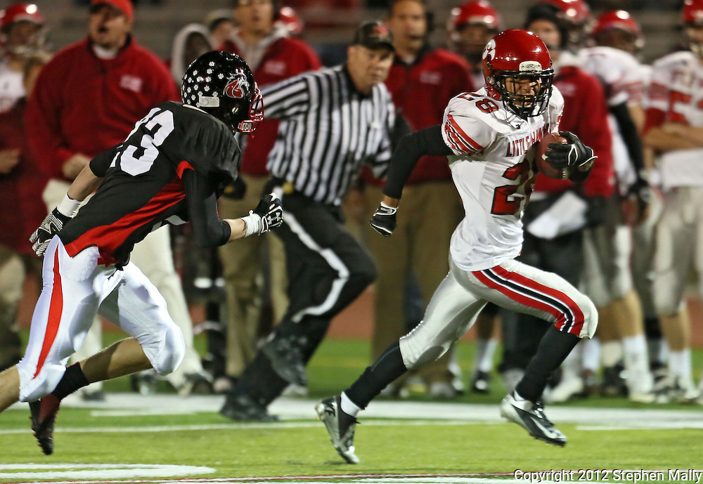 Iowa City High's Bryson Runge (28) looks back at Linn-Mar's Andrew Gassmann (23) on a 34 yard touchdown run during during the game between the Iowa City High Little Hawks and the Linn-Mar Lions at Linn-Mar Stadium in Marion on Friday October 12, 2012.