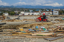 October 3, 2018 - Palu, Central Sulawesi, Indonesia - A resident crossed the damaged road in Talise beach area Palu..A deadly earthquake measuring 7.7 magnitude and the tsunami wave caused by it has destroyed the city of Palu and much of the area in Central Sulawesi. According to the officials, death toll from devastating quake and tsunami rises to 1,347, around 800 people in hospitals are seriously injured and some 62,000 people have been displaced in 24 camps around the region. (Credit Image: © Hariandi Hafid/SOPA Images via ZUMA Wire)