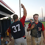 Clarinda A's Spencer Messmore, right, gets congrats from teammate Stuart Smith after sliding into home for a run in the team's 9-1 victory over the Omaha Diamond Spirit.  photo by David Peterson