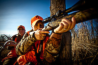 DEER HUNTERS WEARING BLAZE ORANGE AND SHOOTING A RIFLE WHILE A NUNTER IN THE BACK RATTLES ANTLERS