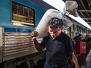 "03 JANUARY 2017 - BANGKOK, THAILAND: A man carries a sack of rice on his shoulder after arriving in Bangkok's Hua Lamphong Train Station Tuesday. The train and bus stations in Bangkok were packed Tuesday, the last day of the long New Year's weekend in Thailand. The New Year holiday in Thailand is called the ""seven deadly days"" because of the number of fatal highway and traffic accidents. As of Monday Jan 2, 367 people died in highway accidents over the New Year holiday in Thailand, a 25.7% increase over the same period in 2016.         PHOTO BY JACK KURTZ"
