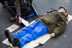 London, UK. 25th November, 2018. Environmental campaigner Phil Kingston, 83, from Extinction Rebellion lies in the road during a Rebellion Day 2 event to highlight 'criminal inaction in the face of climate change catastrophe and ecological collapse' by the UK Government as part of a programme of civil disobedience during which scores of campaigners have been arrested. The event comprised a funeral ceremony in Parliament Square followed by a procession to Downing Street and Buckingham Palace.