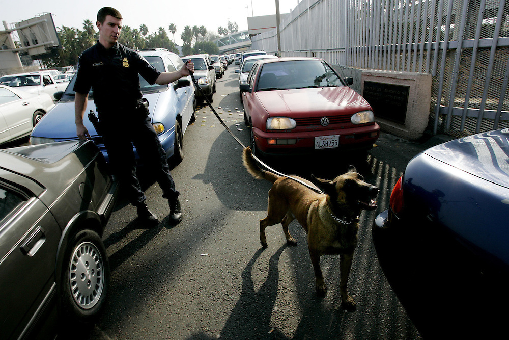 Customs and Border Protection agent Chris Burford inspects vehicles for illegal contraband with his drug sniffing dog  at the U.S. Port of Entry in San Ysidro, Calif.