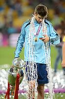 FUSSBALL  EUROPAMEISTERSCHAFT 2012   FINALE Spanien - Italien            01.07.2012 Gerard Pique (Spanien) schleppt den EM Pokal und ein Teil des Tornetz mit sich herum, während er auf seinem Smartphone Neuigkeiten checkt.
