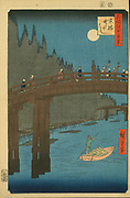 Bamboo Yards, Kyobashi Bridge', 1857. From 'One Hundred Famous Views of  Edo' (Tokyo). Utagawa Hiroshige (1797-1858) Japanese Ukiyo-e artist. By moonlight pedestrians cross bridge. Man poles  boat on river. Bamboos on left.