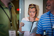 Shannon McGregor, center, a student in the MAA reviews the weekend itinerary before the opening reception in the Ohio University Inn on Thursday, June 25, 2015. © Ohio University / Photo by Rob Hardin