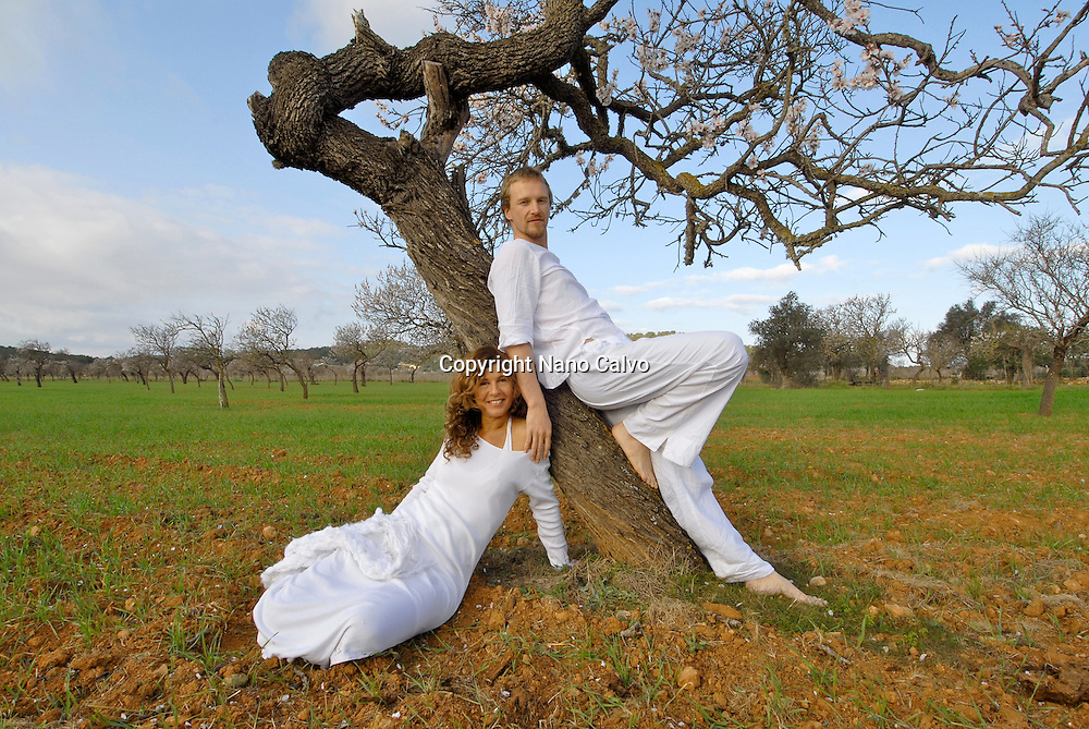 Couple formed by spanish woman and sweedish man, dressed in white, standing by a tree, in the fields of Ibiza, Spain