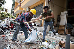 © Licensed to London News Pictures. 10/08/2020. Beirut, Lebanon. Members of the public clean up debris on a backstreet in Mar Mikhael, central Beirut, as part of the aftermath around Beirut city centre following an explosion in Beirut port on Tuesday 4 August. Mar Mikhael and Gemmayzeh were two of the worst affected areas. Photo credit : Tom Nicholson/LNP