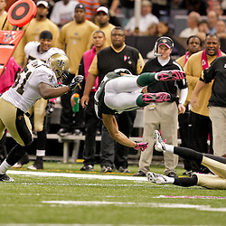 2009 October 04: New York Jets tight end Dustin Keller is propelled into the air by New Orleans Saints cornerback Tracy Porter (22) into linebacker Jonathan Vilma (51) during a 24-10 win by the New Orleans Saints over the New York Jets at the Louisiana Superdome in New Orleans, Louisiana.