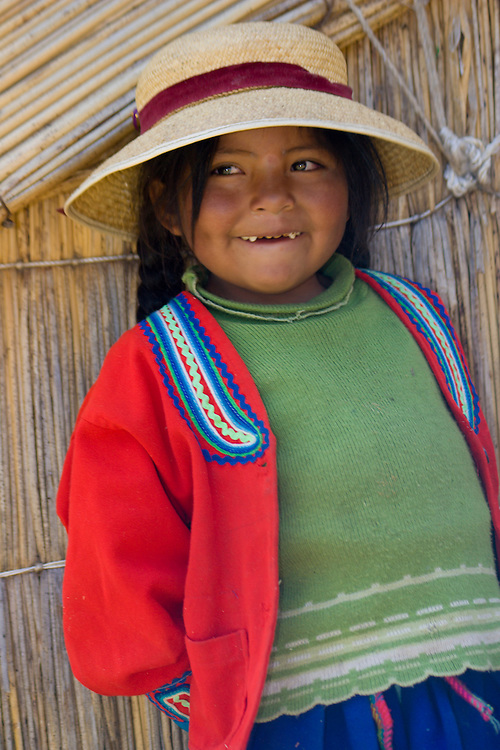 Girl outside straw hut, Uros Islands (also known as Floating Islands or Islas Flotantes), Lake Titicaca, Peru, South America