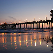 The Huntington Beach Pier is a municipal pier located in Huntington Beach, California. Huntington Beach, also known as Surf City USA, is known for its great surfing. The pier, an icon of the Huntington Beach Coast, is 1,850 feet (560 m) long and is one of the longest public piers on the West Coast.  It has been damaged or destroyed four times; in 1912, 1939, 1983 and most recently on January 17, 1988 destroying the End Cafe for the second time in the decade. The first three piers were constructed from wood, the fourth and current pier is constructed from concrete and designed to withstand 31-foot (9.4 m) waves or a 7.0 magnitude earthquake.  At the end of the Pier is Ruby's Diner which is a 1940's style diner serving hamburgers, shakes, and other classic American food.