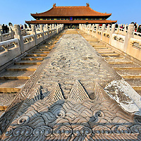 Hall of Preserving Harmony Dragons at Forbidden City in Beijing, China <br /> Leading up to the Hall of Preserving Harmony is a dual staircase.  In the center are elaborate carvings of dragons frolicking with pearl, a symbol of good luck and protector of the throne. Pairs of dragons also represent God and the emperor. This 250 ton slab measures over 54 feet long. The marble-like stone used throughout the Forbidden City was from a quarry at Mount Fang (Fang Shan) over 40 miles away. Each slab was arduously carried to the site by laborers using work animals and then carved by hundreds of artisans.