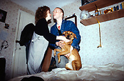 Couple with dog in bedroom, High Wycombe, UK, 1980s.