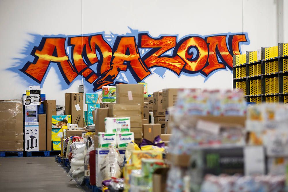 A graffiti styled spray painted Amazon logo is displayed on a wall at the Amazon.com Inc. Prime Now fulfillment center warehouse on Monday, March 27, 2017 in Los Angeles, Calif. The warehouse can fulfill one and two hour delivery to customers. Complex supply chains such as Amazon's and e-commerce trends will impact city infrastructure and how things move through cities. © 2017 Patrick T. Fallon