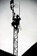 Randy Vanderveen, all rights reserved.Grande Prairie, Alberta.A silhouetted worker climbs a communication tower south of Grande Prairie. .