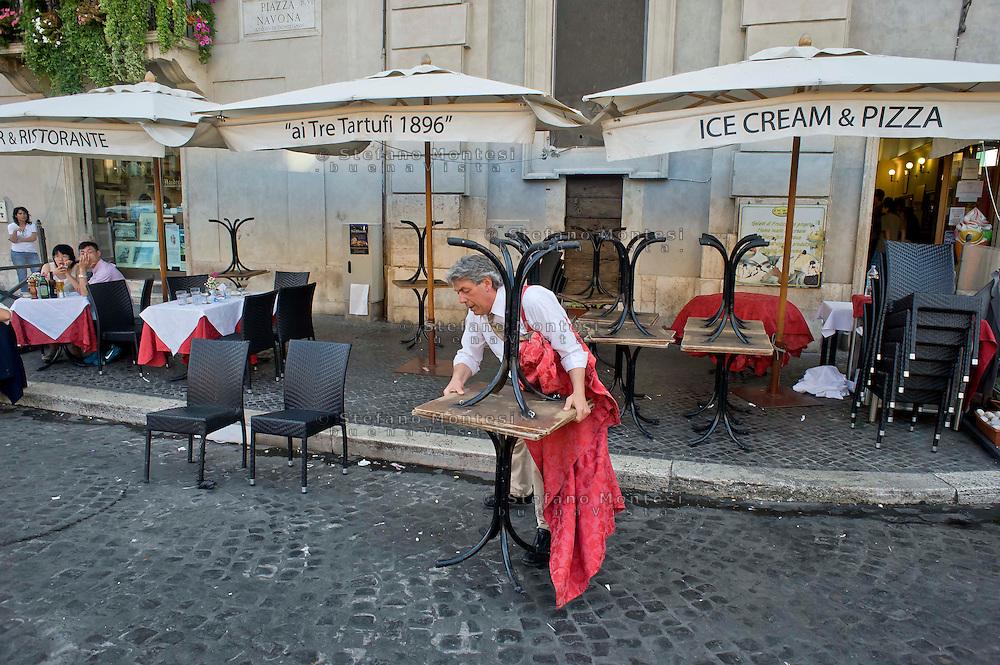 """Roma 6 Agosto 2014<br /> Sono tornati per pochi minuti i dehors a Piazza Navona. I titolari dei ristoranti  hanno deciso di alzare le saracinesche e ripristinare gli spazi esterni, ma posizionando i tavolini nel rispetto dei limiti imposti dalle concessioni del comune di Roma. Ma gli agenti della municipale li hanno bloccati: """"Non sono autorizzati"""". Ristorante TreTartufi chiude con i clienti ancora ai tavoli,  per ordine della Polizia Municipale, perchè non in regola con  i limiti imposti dalle concessioni del comune di Roma.<br /> Rome August 6, 2014 <br /> They came back for a few minutes the dehors in the Piazza Navona. The owners of the restaurants have decided to raise the  rolling shutter and restore the dehors, but by placing the tables within the limits imposed by the concessions of the city of Rome. But the agents of the municipal blocking them: """"They are not unauthorised """".Tre Tartufi  Restaurant close, with the clients to the tables, by order of the Municipal Police, why do not comply with the limits imposed by the concessions of the city of Rome."""