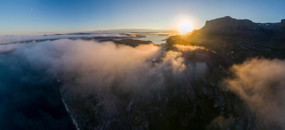 Canada, Labrador, Aerial view of Kaumajet Mountains at Mugford Tickle rising through fog at sunset