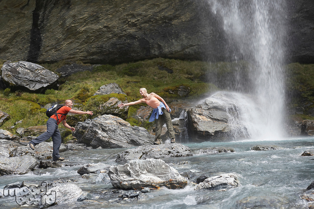Hiker extending arm to another hiker under a waterfall