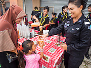 14 JUNE 2015 - NARATHIWAT, NARATHIWAT, THAILAND:  A Thai woman Ranger (paramilitary) gives a milk tea to a Muslim child during a food distribution and outreach before Ramadan in Narathiwat. Ramadan starts June 18. The annual food distribution event is organized by the Southern Peace Media Club, a group of Thai journalists who work in the southern provinces of Pattani, Narathiwat and Yala. An insurgency pitting Muslim extremists against the Thai government has rocked Thailand's southern three provinces since 2001. More than 6,000 people have been killed in the sectarian violence.   PHOTO BY JACK KURTZ