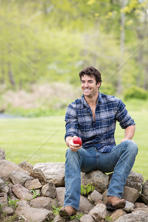 good looking man sitting on a stone wall