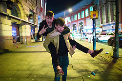 © Licensed to London News Pictures . 01/01/2018. Manchester, UK. A man gives another a piggy back on Withy Grove . Revellers celebrate the start of the New Year in Manchester City Centre . Photo credit: Joel Goodman/LNP