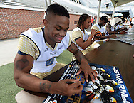 August 1, 2013 - Atlanta: Georgia Tech defensive back Louis Young signs a poster during Georgia Tech fan Day at Bobby Dodd Stadium on Saturday, August 8, 2013. JOHNNY CRAWFORD / JCRAWFORD@AJC.COM