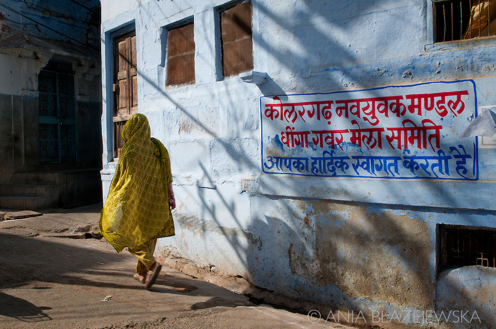 India, Jodhpur. A woman wearing a yellow sari walking near a blue wall in the old part of Jodhpur.