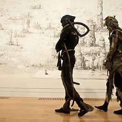 London, UK - 1 october 2012: performers of the 'Odd Man Out 2011' by Spartacus Chetwynd looks at a piece of work by Paul Noble during the Turner Prize 2012 press preview at the Tate Britain. The exhibition features work by four shortlisted artists: Spartacus Chetwynd, Luke Fowler, Paul Noble and Elizabeth Price. The winner of the prize will be announced during a live broadcast of the award ceremony on Channel 4 on the evening of Monday 3 December 2012. The exhibition is open from 2 October 2012 to 6 January 2012. Images are available for sale here, on Barcroft Media, Alamy, Demotix, Press Association and Corbis.